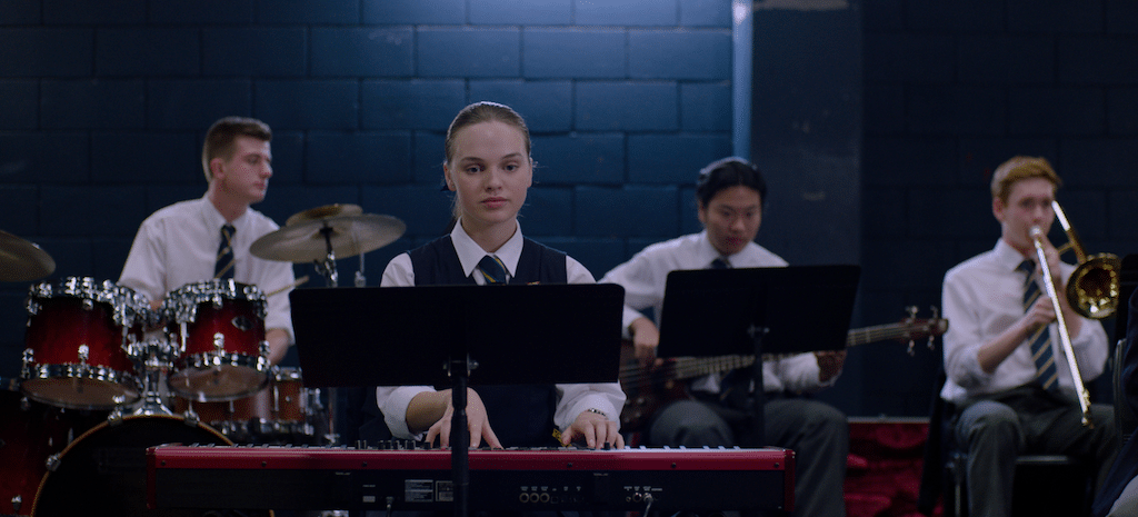 Genevieve (played by Odessa Young) plays in her school jazz ensemble in HIGH LIFE.