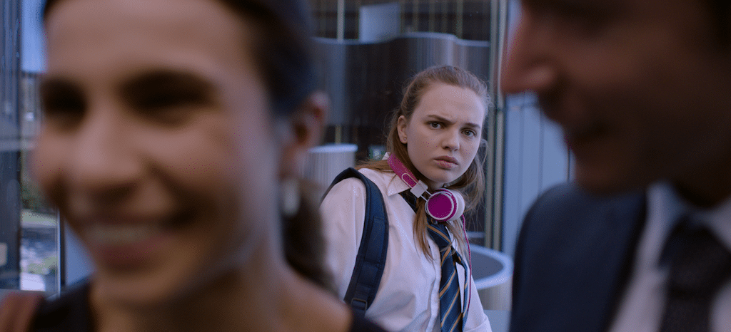 Genevieve (played by Odessa Young) watches an office couple with disdain in HIGH LIFE.